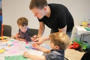 Volunteer helping two boys